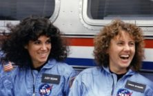 Image of Judith Resnik and Christa McAuliffe. Resnik is on the left and has curly black hair. McAuliffe is on the left and has curly blonde hair. Both are wearing light blue NASA jumpsuits and smiling at something off-camera to the left.